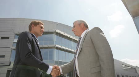 опытный : Two businessmen greeting each other by handshake in urban environment Стоковые видеозаписи