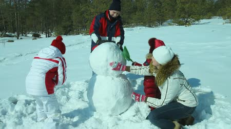 kardan adam : Energetic family of four making a snowman on winter holidays