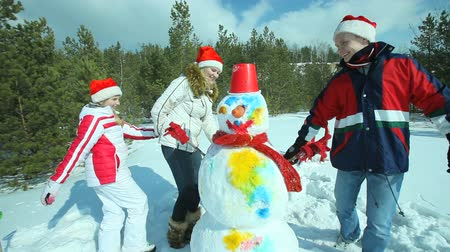 kardan adam : Joyful family dancing around a colorful snowman on a sunny winter day Stok Video