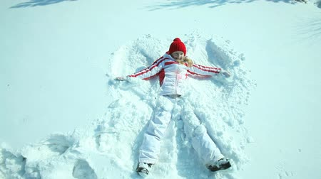snow angel : Teenage girl falling in the snow and making a snow angel Stock Footage