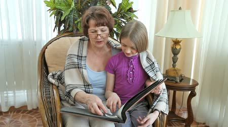 бабушка : Grandma and her lovely granddaughter spending time together looking at old photographs