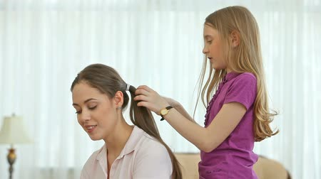 fryzjerstwo : Pretty little girl doing her sisters hair