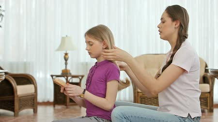 fryzjerstwo : Girl combing and braiding her little sisters hair