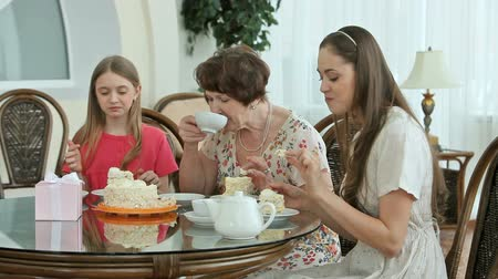 babcia : Grandmother and granddaughters enjoying sweet cake and tea together Wideo