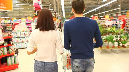 aisles : Couple walking through shopping mall with a market cart