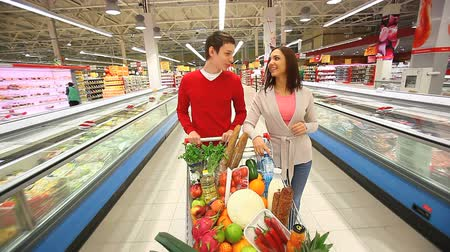 kordé : Cheerful couple walking through mall with a cart full of groceries Stock mozgókép