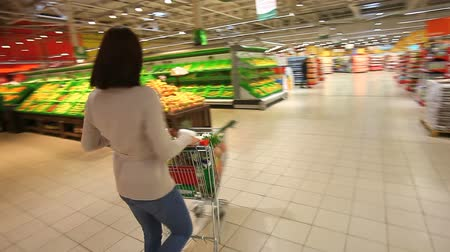 супермаркет : Female shopper having fun in mall swinging the cart full of groceries