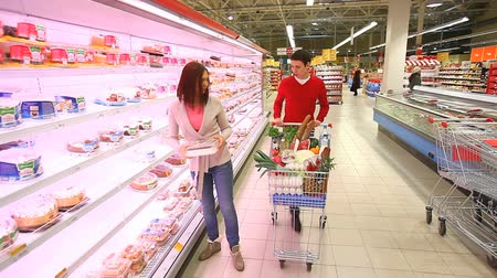супермаркет : Young woman taking products from the shelves and putting them into cart pushed by guy