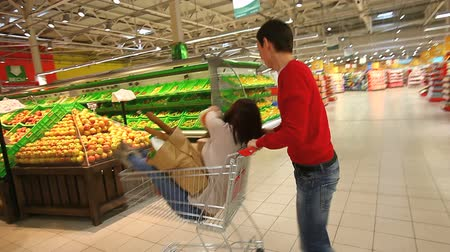 corredor : Guy pushing his girlfriend in a trolley as if in a car through the mall