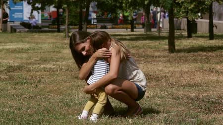 мама : Lovely little girl running to her mom who hugs and kisses her with affection Стоковые видеозаписи