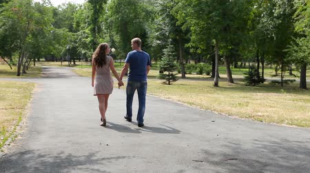 társkereső : Young people holding hands and going away along the park lane