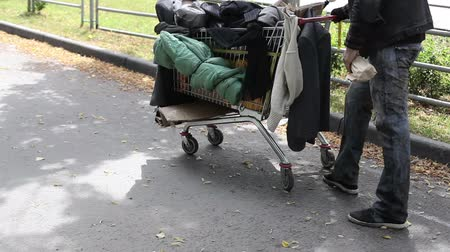 csavargó : Homeless guy with a limp pushing a shopping cart full of dirty clothes Stock mozgókép
