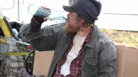 csavargó : Guy in ragged clothes drinking water from a plastic bottle