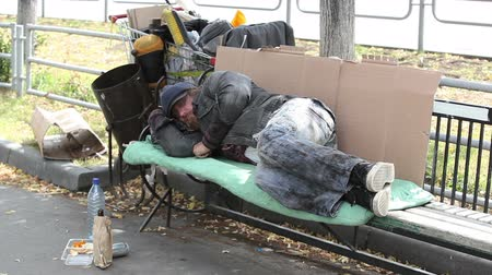 csavargó : Homeless man having a rest lying on the bench with his belongings nearby