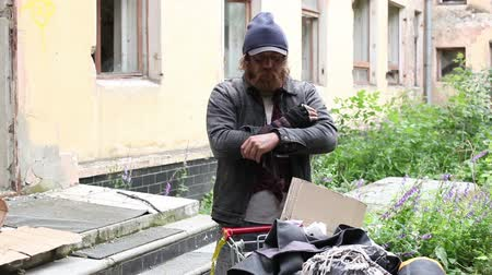 hajléktalan : Portrait of a homeless man standing by the cart with his possessions and looking at the camera Stock mozgókép
