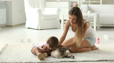 carinho : Mom and daughter playing with their pet at home