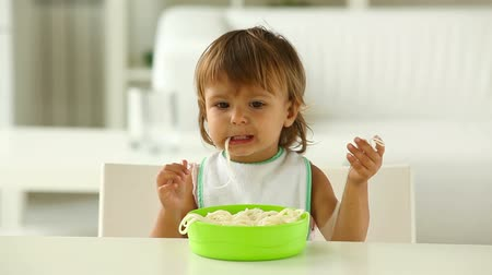 голодный : Charming cutie eating spaghetti with fingers and enjoying it