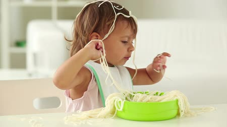 голодный : Little girl making a total mess of spaghetti Стоковые видеозаписи