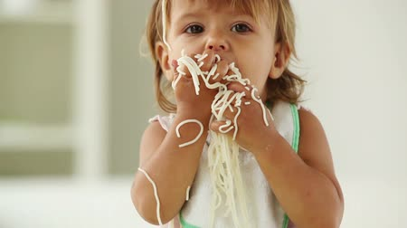 fome : Close-up of a hungry little girl devouring noodles and making a mess Stock Footage