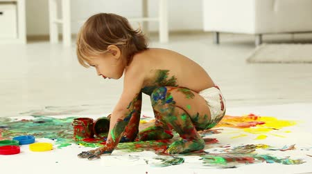 little : Cute child playing with paints making quite a mess Stock Footage