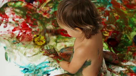 nepořádek : The above-view of a creative kid making a mess while finger-painting