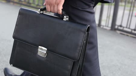 corporate : Close-up of a commuter with a briefcase crossing the city bridge