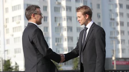 tratar : Mature partner meeting his young colleague, shaking hands and going away Vídeos
