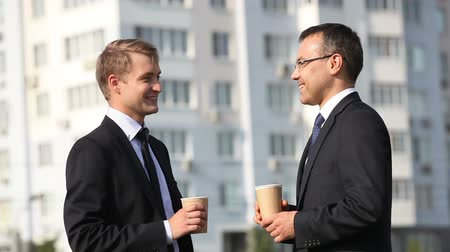 perfil : Cheerful businessmen having a break drinking coffee outdoors Stock Footage