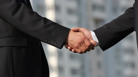tratar : Close-up of business people shaking hands firmly developing business bonds