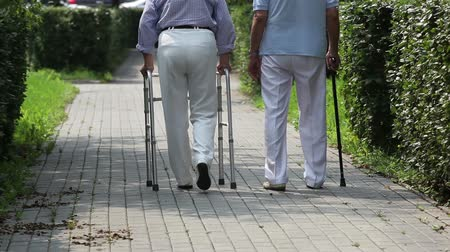 senior lifestyle : Elderly couple taking steps together with a help of a walker and a cane