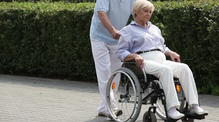 rokkant : Retired man taking his disabled wife for a walk in the park Stock mozgókép
