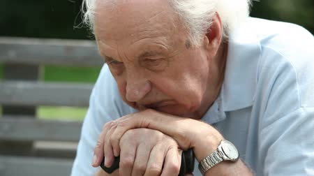 senior lifestyle : Close-up of a pensive old man sitting all alone outdoors Stock Footage