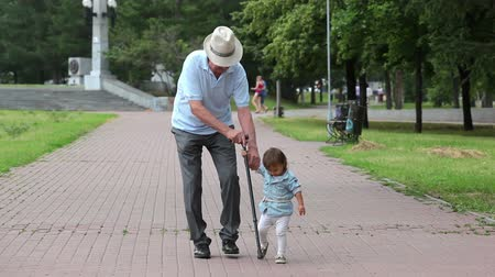 helping : Granddaughter helping his grandfather to walk with a cane
