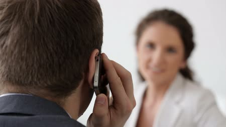 диалог : Colleagues conversing when a businessman receives a phone call