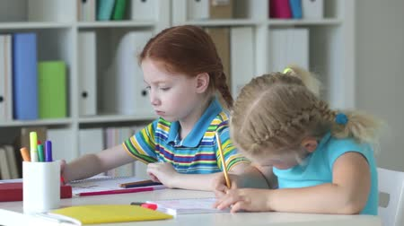 birincil : Little blonde girl drawing with enthusiasm, her classmate watching her