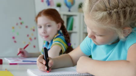элементарный : Close-up of a serious girls drawing with a felt-tip markers