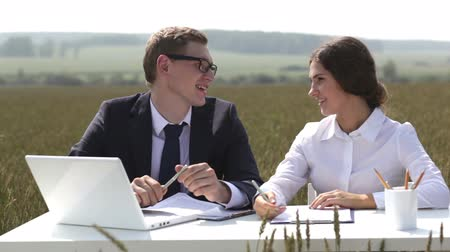 beyaz yakalı işçi : Tilt of positive business people sitting at the desk in the midst of a wheat-field Stok Video