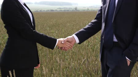 parceria : Business people shaking hands confirming their partnership in the countryside