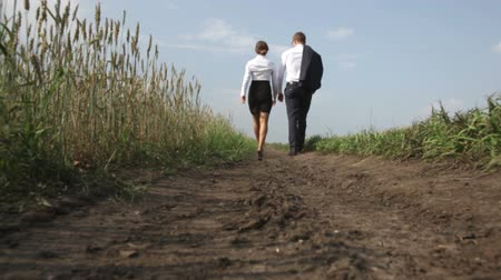 perspectiva : Relaxed people in formalwear following the country road between the fields