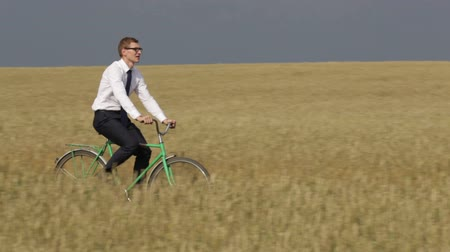 kurier : Businessman speeding up while cycling across the wheat field