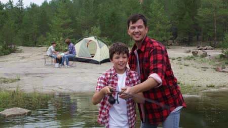 kamp : Family of campers enjoying their leisure, father and son fishing