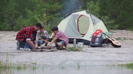 kamp ateşi : Camping family making a fire reflecting in the water Stok Video