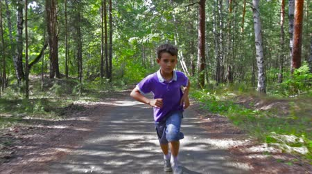 pursue : Serious lad running through the forest as if pursuing someone