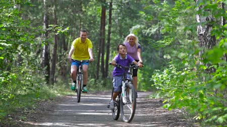 bisiklete binme : Energetic parents and their kid enjoying a family bicycle ride