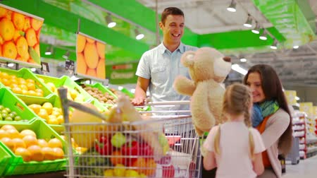 grocery : Lovely girl bringing a teddy bear to her parents in the supermarket