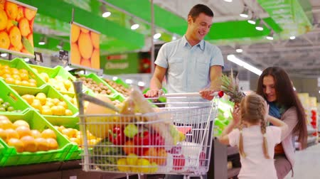супермаркет : Happy family doing shopping, lovely girl bringing pineapple and putting it into the trolley
