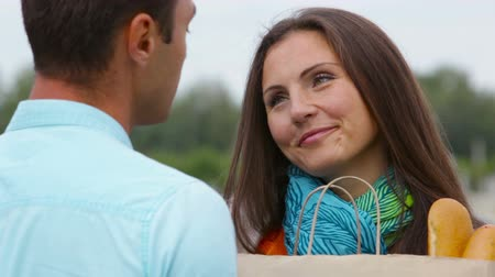transportar : Lovely couple flirting, guy helping young woman to carry her groceries Stock Footage