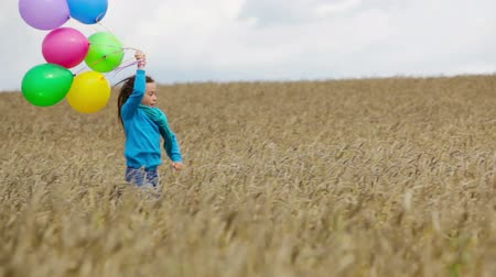 életerő : Charming girl holding a bunch of colorful balloons running in the countryside