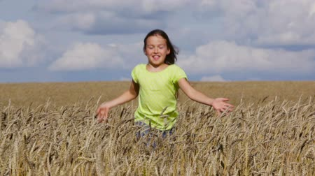 cultivo : Cute child jumping out of wheat and running towards the viewer