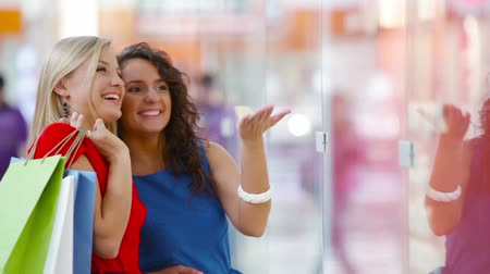 зубастая улыбка : Ladies having fun standing by the shopping window in the mall
